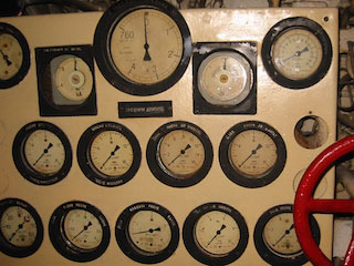 A wall in a submarine with many dials the measure various things.